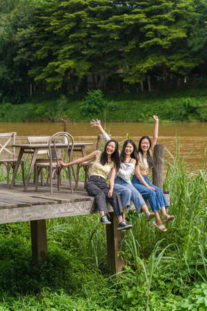 Three happy young Asian female friends sitting enjoying themselves on the wooden deck  by a river with big trees in background, friendship or young happy lifestyle concept Stok Fotoğraf