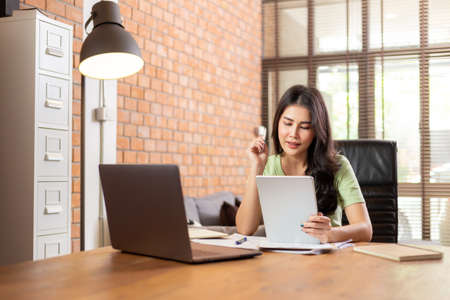 Happy young Asian businesswoman siting in her home living room office smiling while working on her business ideas while holding her computer tablet and its stylus pencil, work from home business concept