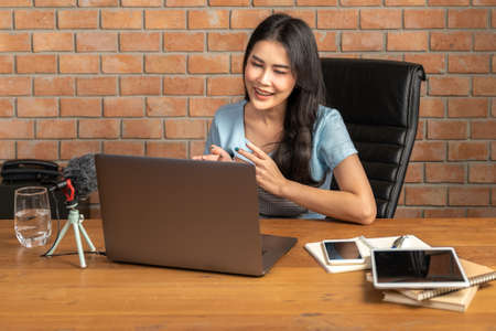 Happy young attractive woman working or learning online through her laptop computer at home in her living room during the pandamic lockdown, distant learning or virtual business concept