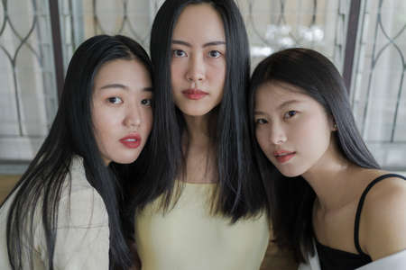 Close up portrait of three beautiful young Asian female friends casually pose for the camera together inside a rustic room in natural light, young chic Asian modern lifestyle concept