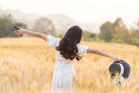 Back view of young long hair woman in white dress standing alone stretching her arms out and holding her hat and phone in the golden color barley field during golden hour, room for copy space