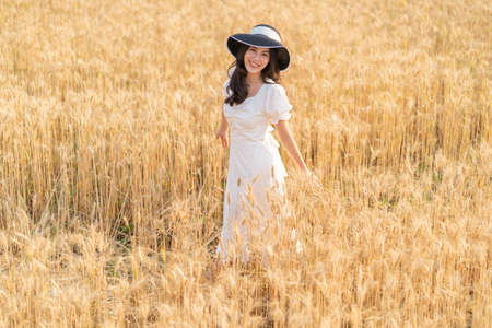 Happy young beautiful woman wearing black hat and white dress enjoying herself walking in the golden barley filed on a late afternoon, room for copy space