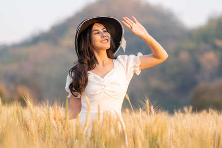 Happy young beautiful woman wearing black hat and white dress holding up her hand to block to sun shining on her face while enjoying herself walking in the golden barley field on a late afternoon, room for copy space