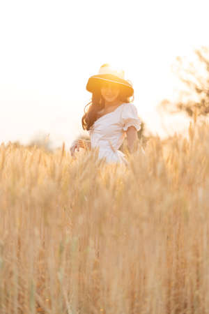 Happy young beautiful woman wearing black hat and white dress enjoying herself walking in the golden barley filed on a late afternoon, back lit, room for copy space Stok Fotoğraf