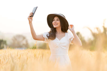 Happy young beautiful woman wearing black hat and white dress taking selfie while walking in the golden barley filed on a late afternoon, back lit, room for copy space