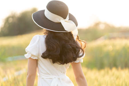 Back view of young woman wearing black hat and white dress walking alone at a barley field on a late afternoon before sunset, warm golden hour light and room for copyspace