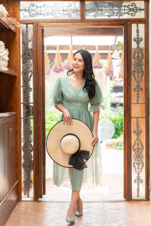 Happy young beautiful woman gracefully walking into her house while holding her straw hat and smiling at unseen person outside, lifestyle concept Stok Fotoğraf