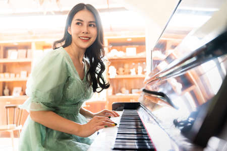 Happy young beautiful woman smiling while playing piano at home during a warm sunny day, happy lifestyle concept