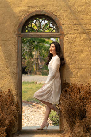 Happy young beautiful woman in soft white dress leaning on the door frame of her rustic garden green house on a bright sunny day, lifestyle concept