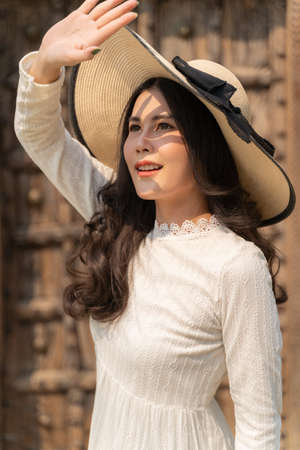 Happy young beautiful woman in soft white dress and big straw hat holding up her hand to block the sun light and shadow casting down on her smooth skin of her face, beautiful skin or healthy concept