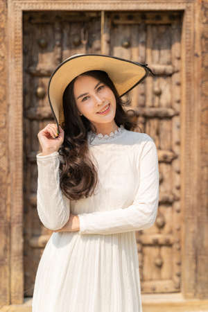 Happy young beautiful attractive asian woman in white dress and straw hat smiling at camera while standing ouside a rustic wooden building in the sun, happy lifestyle concept