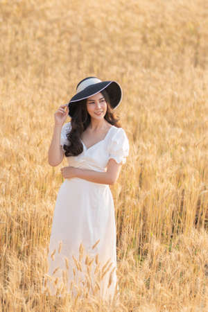 Happy young beautiful Asian woman in white dress and straw hat standing in the middle of the barley field on a bright sunny evening, lifestyle concept Stok Fotoğraf