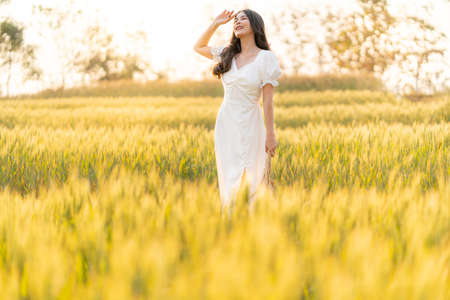 Happy young beautiful Asian woman in white dress standing in the barley field enjoying her time outdoor alone during sunset, lifestyle concept