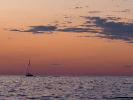 sunset over Lake Michigan with silouhette of rocks and driftwood