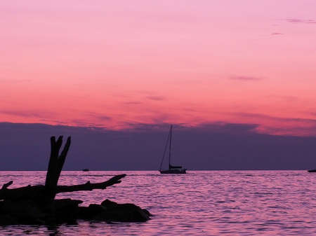 pink sunset over Lake Michigan with silouhette of rocks and driftwood