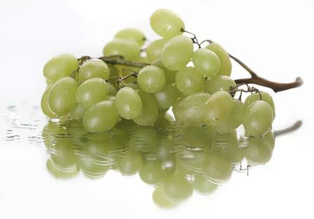 Bunch of grapes on a mirrored surface
