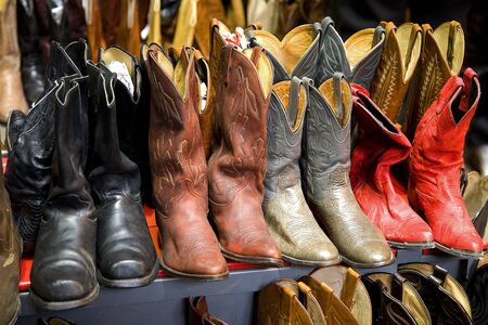 A collection of cowboy boots in rows
