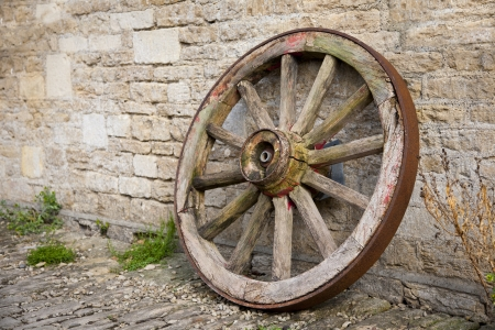 An old wooden wagon wheel leaning up against a stone wall