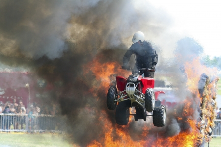 A quad bike at an event jumping through fire Stock Photo