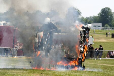 A motorcyclist at an event jumping through fire