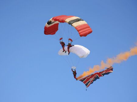 Three parachutist skydiving and trailing a large Union flag with a colored smoke trail
