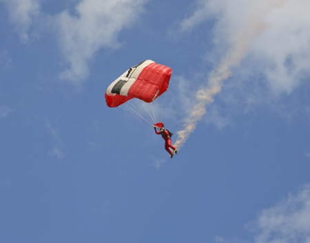 A skydiver trailing coloured smoke behind him