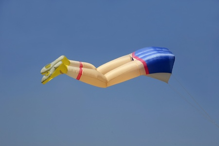 Leg shaped kite flying in a clear blue sky