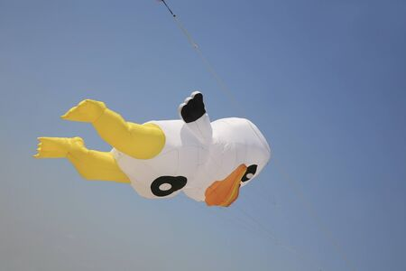 A kite in the shape of a cartoon duck flying in the sky photo