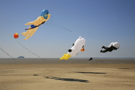 Selection of various shaped kites flying in a clear blue sky Stock Photo
