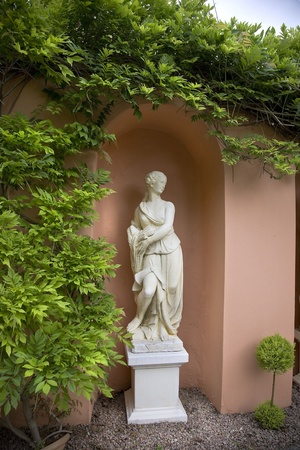An alabaster statue of a woman in a garden archway surrounded by a climbing plant