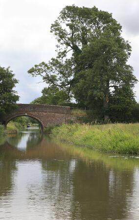 Visi�n a lo largo del canal magn�fico de la uni�n en Leicestershire con uno de sus muchos puentes