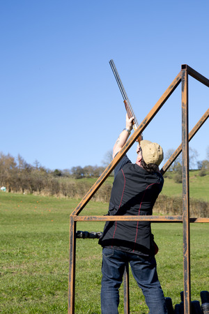 A clay shooter in the stand aiming at the clay pigeon target