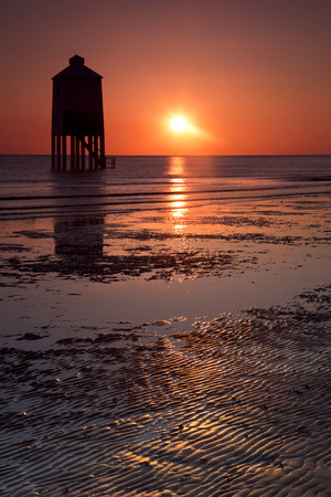 brean: Sunset over the wooden lighthouse on Burnham on Sea beach in Somerset, UK Stock Photo