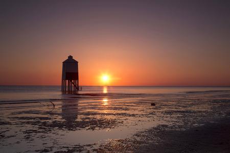 Puesta de sol sobre el faro de madera en Burnham en la playa de mar en Somerset, Reino Unido