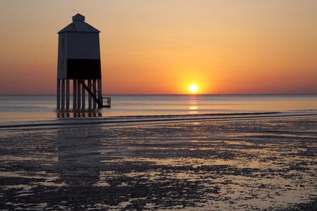 brean beach: Sunset over the wooden lighthouse on Burnham on Sea beach in Somerset, UK Stock Photo