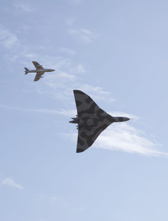 weston super mare: WESTON SUPER MARE, UK - JUNE 21: Avro Vulcan Bomber aircraft XH558 escorted by a Hawker Hunter jet participates in the combined Air ShowArmed Forces event June 21, 2015 at Weston Super Mare, Somerset, England.This is its last year of flying before being