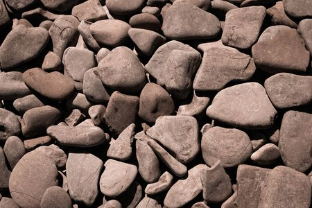 An assortment of brown coloured pebbles on a beach