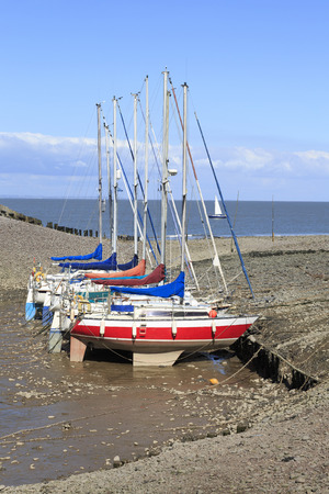 Colourful yachts moored in a line at low tide in a harbour in Somerset,UK