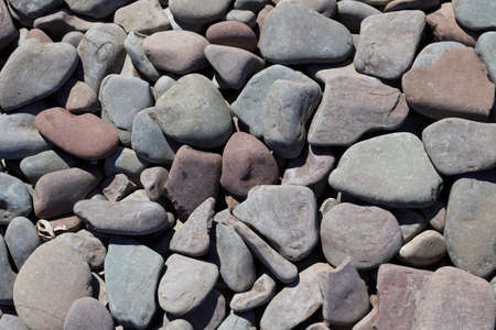 A selection of grey and pink coloured pebbles on a beach