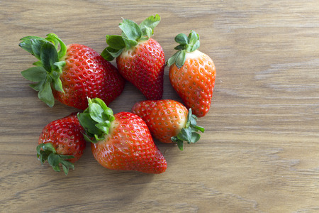 A groups of tasty fresh strawberries on a wooden background Stock Photo