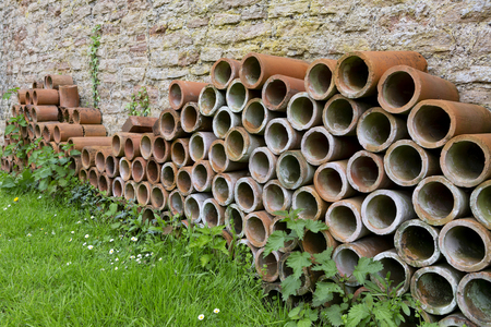 A stack of terracotta tube planters for growing plants stacked up against a wall