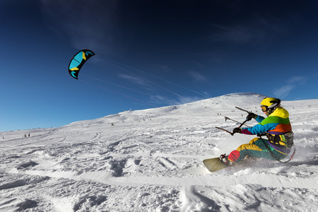 kiting: Snowboarder with kite on free ride. Sheregesh resort, Siberia, Russia