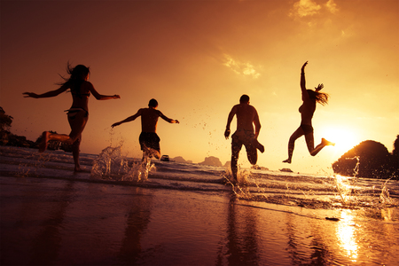 holiday trip: Group of happy young people is running on background of sunset beach and sea