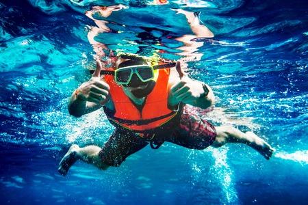 Man schwimmt unter Wasser in einer Schwimmweste und eine Maske zum Schnorcheln