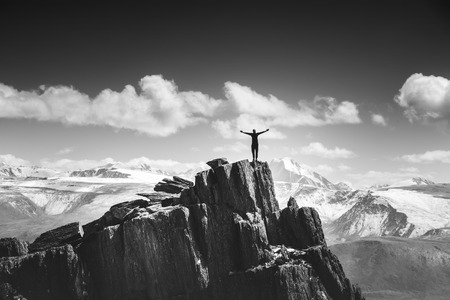 Winner concept. Man stands on the top of mountain on mountains backdrop