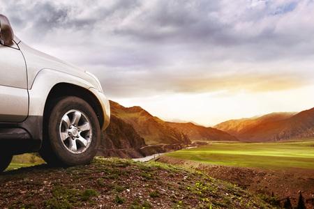 オフロード車のコンセプト。山と夕日の背景に大きな車ホイール 写真素材