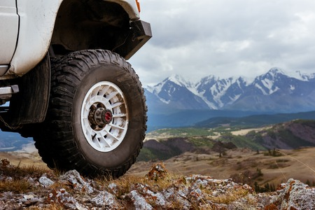 Big car wheel is standing on the rocks on mountain backdrop. Altay mountains, Siberia, Russia Stock Photo