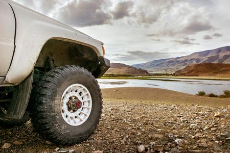 큰 SUV 자동차 바퀴 산 호수를 배경으로 의미합니다. 스톡 콘텐츠