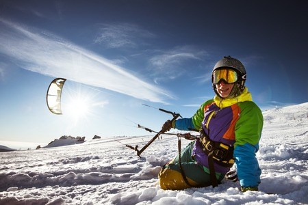 snowkiting: Happy snowboarder with kite lies in snowdrift. Sheregesh resort, Siberia, Russia