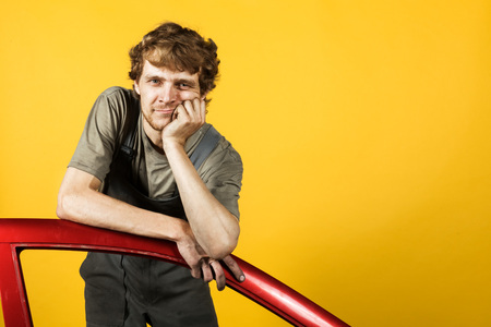 Handsome mechanic leans on the red cars door and looking forward on the background of yellow bright wall Stock Photo